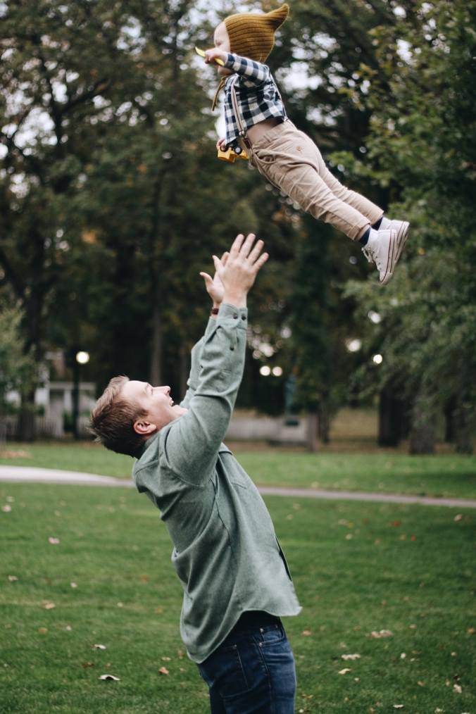 A man tosses his young child into the air with joy. Photo by Bri Heiligenthal