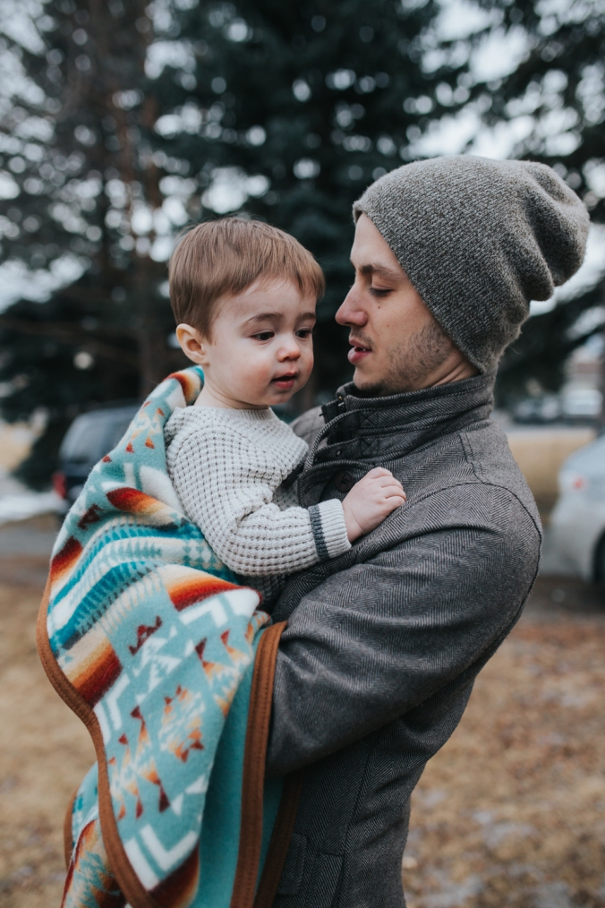 A young father holds his child, who is wrapped in a Pendleton child's blanket. Photo by Grace Adams